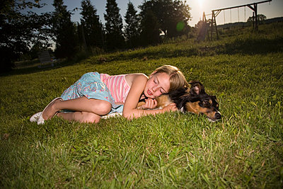 Girl snuggling against dog in the meadow - p1207m1111708 by Michael Heissner