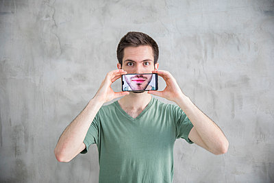 Young man is holding smartphone with his mouth on the display - p276m2110770 by plainpicture