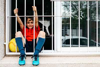 Boy with soccer ball at the window without being able to leave the house to play - p300m2188778 by Josep Rovirosa