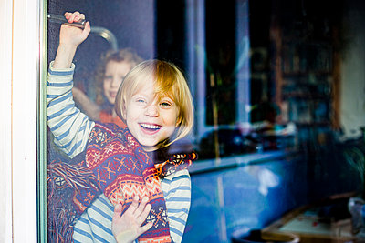Cheerful girl with brother seen through glass door - p300m2275356 by Irina Heß