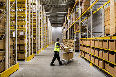 Full length of young warehouse worker pushing cart on aisle in industrial building - p426m2018851 by Maskot