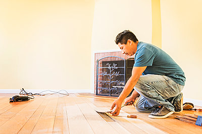 Hispanic man installing floors in new house - p555m1408525 by Sollina Images