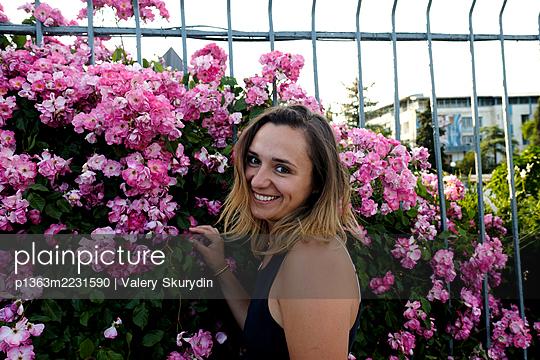 Smiling woman near flowers  - p1363m2231590 by Valery Skurydin