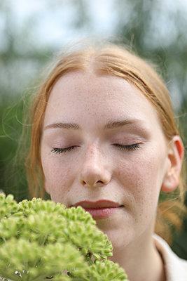 Frau riecht an Blume - p045m2193004 von Jasmin Sander