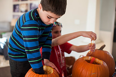 brother and sister preparing their pumpkins to carve for halloween - p1166m2073851 by Cavan Images
