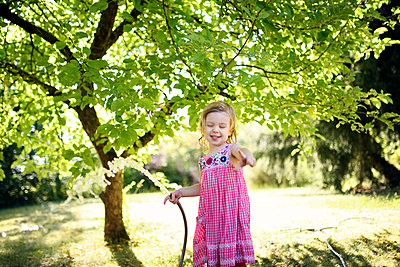 Happy girl gesturing while holding watering pipe in garden - p300m2273736 by Biederbick&Rumpf