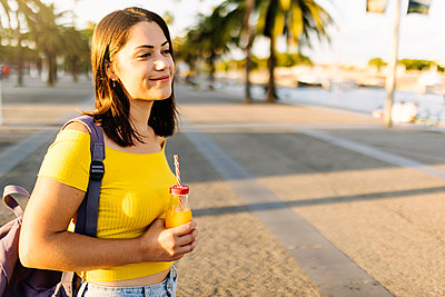 Young woman with orange juice standing on street - p300m2294268 by Xavier Lorenzo