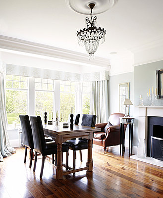 Black leather chairs at table in dining room with polished wooden floor in Harrogate home - p349m790390 by Brent Darby