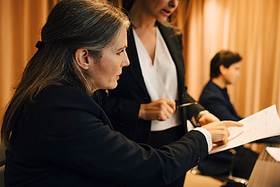 Businesswoman discussing over legal document with female lawyer in office - p426m2270844 by Maskot