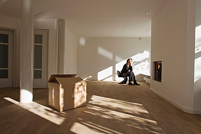 Woman sitting on chair in empty room - p429m802917f by Christine Schneider