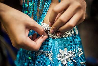 Young Woman Securing Sequined Dress With Safety Pin - p694m785377 by Aaron Joel Santos