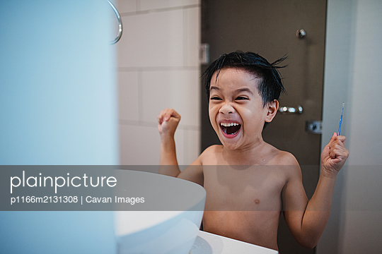 Asian boy combing hair in front of mirror - p1166m2131308 by Cavan Images