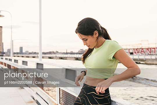 Woman taking a break after workout down by waterfront pier - p1166m2292588 by Cavan Images