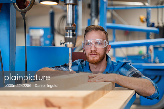 Portrait of carpenter wearing protective goggles drilling wooden plank - p300m2242296 by Daniel Ingold