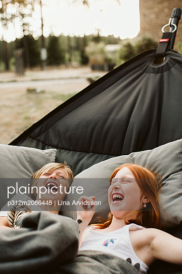 Brother and sister lying in hammock - p312m2086448 by Lina Arvidsson