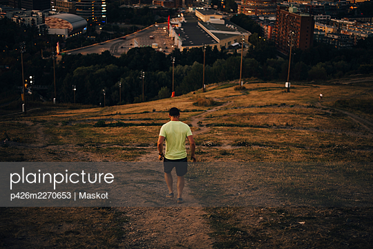 Rear view of male athlete walking on land during sunset - p426m2270653 by Maskot