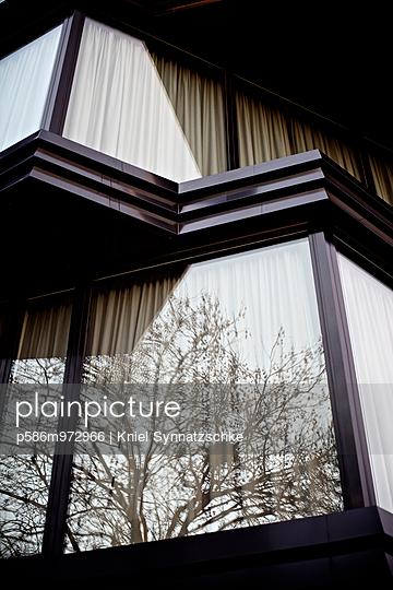 Bäume spiegeln sich in den Fensterscheiben eines Wohnhauses - p586m972966 von Kniel Synnatzschke