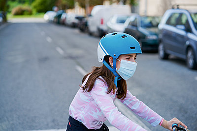 Girl in mask riding kick scooter - p1166m2201409 by Cavan Images