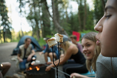 Teenage girl outdoor school students blowing on toasted marshmallow at campsite campfire - p1192m1490921 by Hero Images