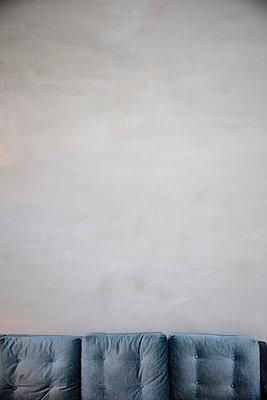 Blaues Sofa vor Lehmwand - p1212m1091999 von harry + lidy