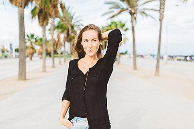 Smiling young woman on waterfront promenade - p300m1228208 by Giorgio Fochesato