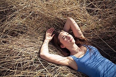 Relaxed young woman lying in meadow - p300m2104313 by Philipp Nemenz