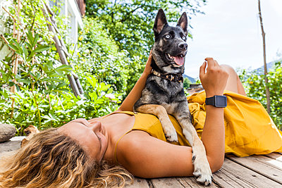 Husky shepherd mongrel dog and his mistress lying on wooden board - p300m2121946 by Tom Chance