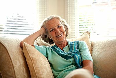 Portrait of senior woman (55-65) relaxing on sofa, London, United Kingdom - p300m2287141 von LOUIS CHRISTIAN