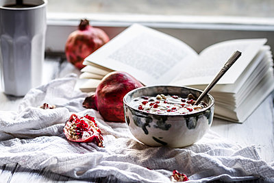 Healthy breakfast with pomegranate in yogurt, Coffee and opened book - p300m874021f by Susan Brooks-Dammann