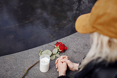 Woman praying over rose and candle - p312m2285487 by Plattform