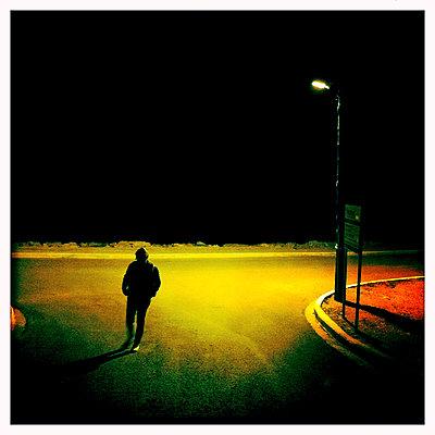 Mann auf einer dunklen Straße - p979m1146569 von Werner Gritzbach