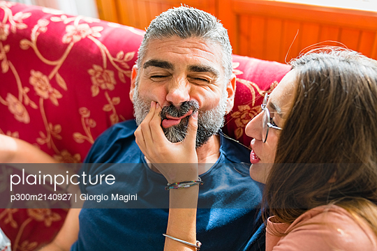 Mischievous daughter with father on couch at home - p300m2140927 by Giorgio Magini