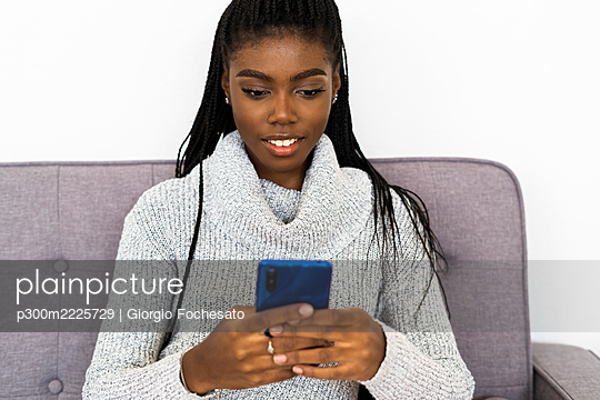 Woman text messaging on smart phone while sitting at home - p300m2225729 by Giorgio Fochesato