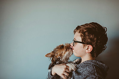 Yorkshire Terrier licking boy's face against wall at home - p1166m1416306 by Cavan Images