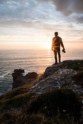 Rear view of silhouette man with camera standing on cliff at beach against cloudy sky during sunset - p1166m1521145 by Cavan Images