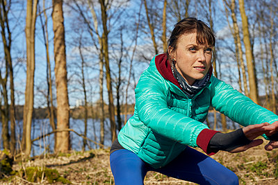 Sporty woman performs fitness exercise in the woods - p1491m2175998 by Jessica Prautzsch