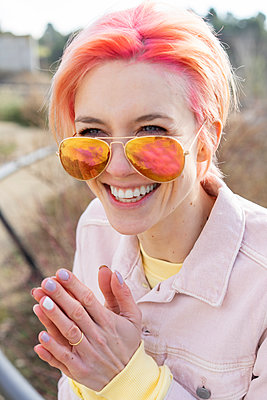 Portrait of young laughing woman, sun glasses and pink jeans jacket - p300m2023904 by VITTA GALLERY