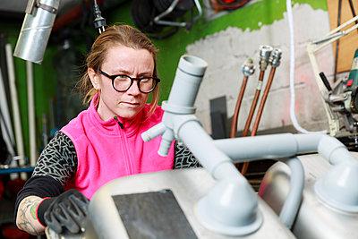 Female plumber working in workshop - p312m2262870 by Phia Bergdahl
