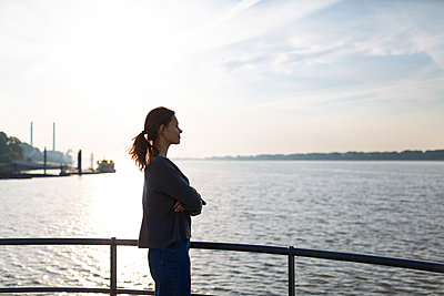 Young woman looks out over the Elbe river - p341m2210411 by Mikesch