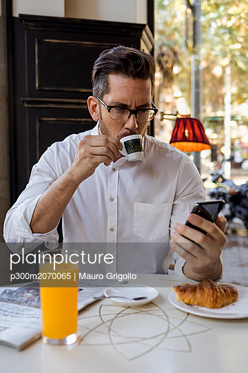 Businessman having breakfast in a cafe and checking cell phone - p300m2070065 by Mauro Grigollo