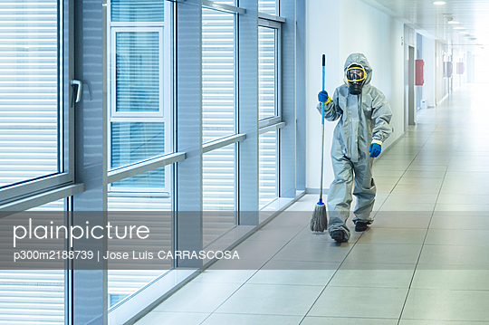Cleaning staff walking with cleaning mop in corridor, wearing protective clothing - p300m2188739 by Jose Luis CARRASCOSA