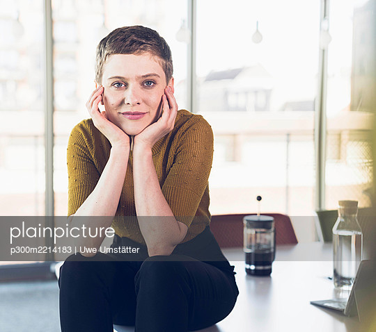 Portrait of smiling businesswoman sitting on desk in office - p300m2214183 by Uwe Umstätter