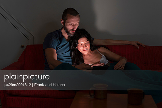 Hipster couple using digital tablet on sofa - p429m2091312 by Frank and Helena