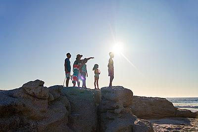 Family standing on rocks at sunny beach - p1023m2200866 by Trevor Adeline