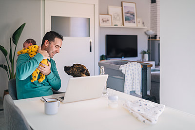 Father carrying son while looking at dog in home office - p300m2267786 by Manu Padilla Photo
