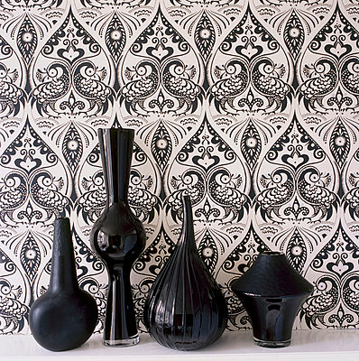 Black and white patterned wallpaper with black glassware and ceramic vases on a shelf - p349m695188 by Emma Lee