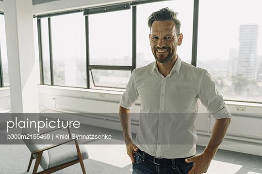 Portrait of confident mature businessman in empty office - p300m2155468 by Kniel Synnatzschke