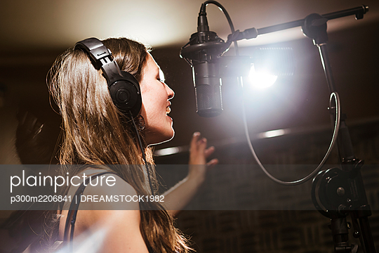Singer with headphones at microphone in recording studio - p300m2206841 by DREAMSTOCK1982