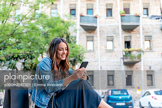 Smiling female tourist using smart phone while sitting in city - p300m2287321 by Emma Innocenti