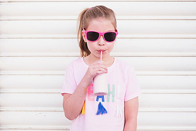 Young girl wearing pink sunglasses drinking pink milk through a straw - p1166m2136092 by Cavan Images